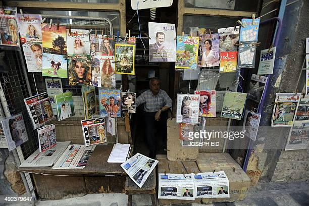 A Syrian man sells magazines and newspapers at his shop in Syria's Mediterranean port city of Latakia on May 19 2014 More than 162000 people have...