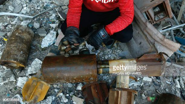 A Syrian man shows remnants of rockets reportedly fired by regime forces on the rebelheld besieged town of Douma in the eastern Ghouta region on the...