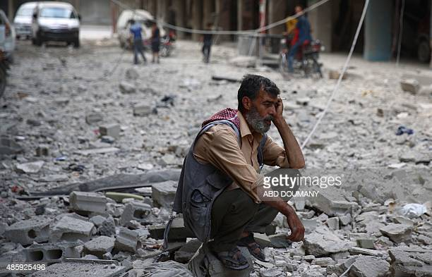 A Syrian man sits amid the rubble of destroyed buildings following reported air strikes by regime forces in the rebelheld area of Douma east of the...