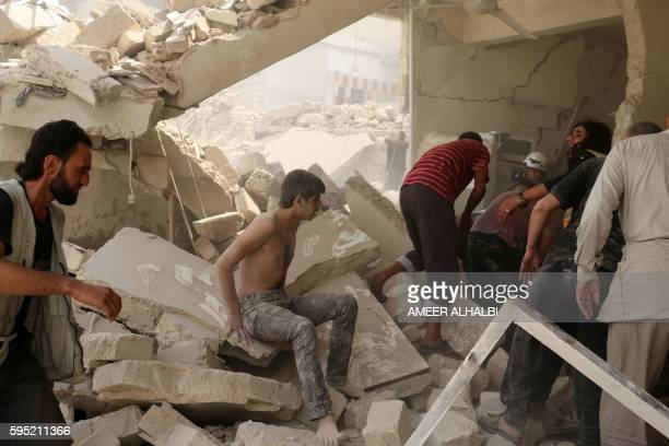 A Syrian man sits in shock in the rubble of a building following a barrel bomb attack on the Bab alNairab neighbourhood of the northern Syrian city...