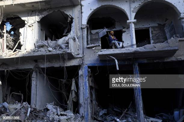 Syrian man sits on the balcony of a damaged building in the northern Syrian city of Raqa on January 16 2018 after a huge military operation led on...