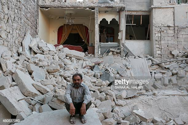 A Syrian man sits on the rubble of a destroyed building following reported air strikes by government forces in the northern city of Aleppo on June 13...