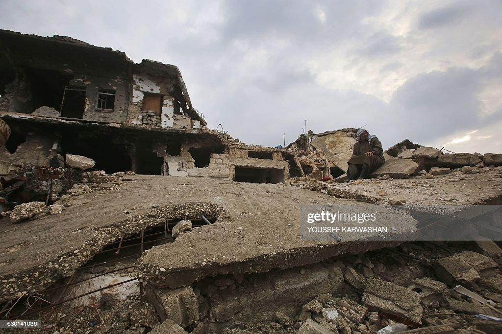 A Syrian Man Sits On The Rubble Of His House In Aleppou0027s Al Arkoub  Neighbourhood