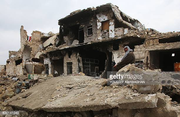 Syrian man sits on the rubble of his house in Aleppo's AlArkoub neighbourhood on December 17 after progovernment forces retook the area from rebel...