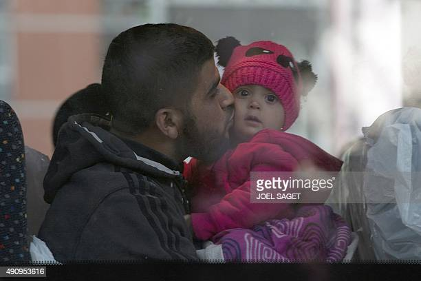 A Syrian man sits with his child as mainly Syrian refugees are removed from their make shift camp by the French authorities at the Porte de SaintOuen...