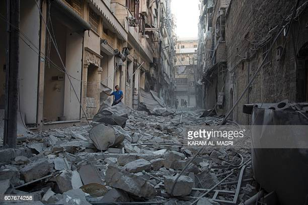 Syrian man stands in the rubble of destroyed buildings following an air strike in Aleppo's rebelcontrolled neighbourhood of Karm alJabal on September...