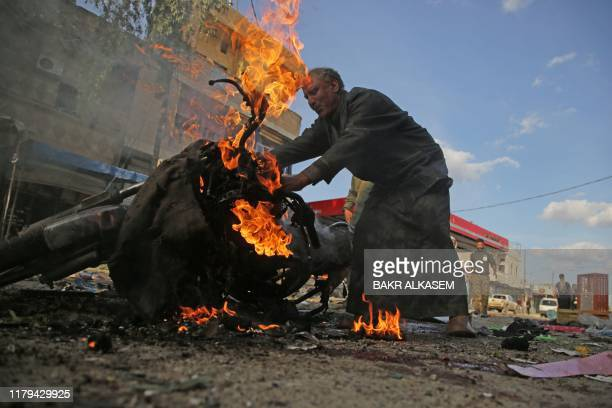 Syrian man stands next to a burning motorcycle at the site of a car bomb explosion in the northern Syrian Kurdish town of Tal Abyad, on the border...