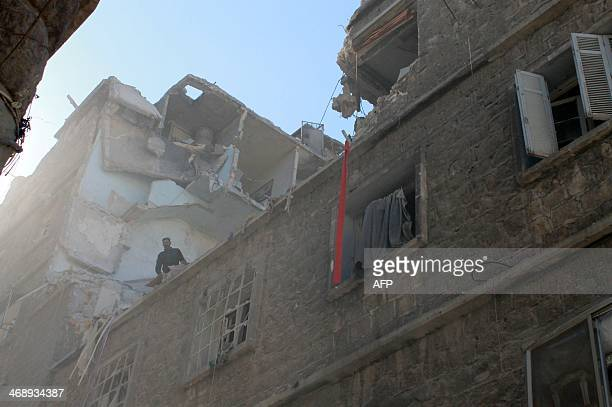 A Syrian man stands on a damaged building following a reported air strike by government forces in the northern city of Aleppo on February 12 2014 A...