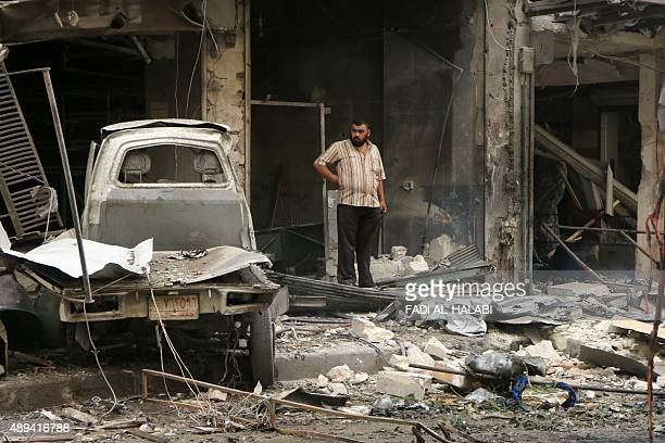 A Syrian man stands on a street amid the rubble of collapsed building following reported bombings by government forces on a market on the rebel held...