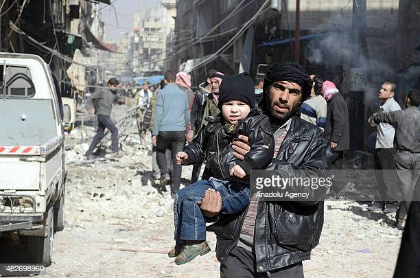 Syrian man takes his son away after Syrian regime's air forces' air attack on East Ghouta region with 'Vacuum Bomb' that killed at least 10 people...