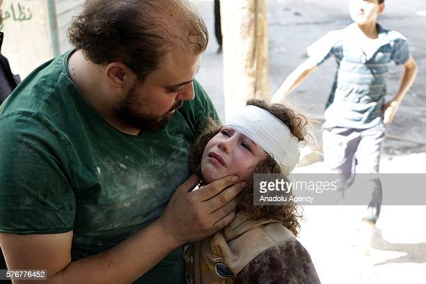 Syrian man tries to calm down a wounded g after the war-craft belonging to the Russian army bombed the opposition controlled residential area at the...