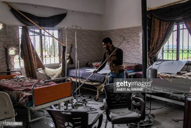 Syrian man tries to clear rubble at a damaged ward in a hospital that was hit by a reported regime air strike in the town of Saraqib in the northern...