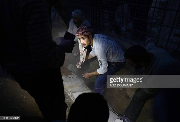 A Syrian man uses a phone to light the grave of fifteenyearold Jihad who died following a reported government air strike during his burial in the...