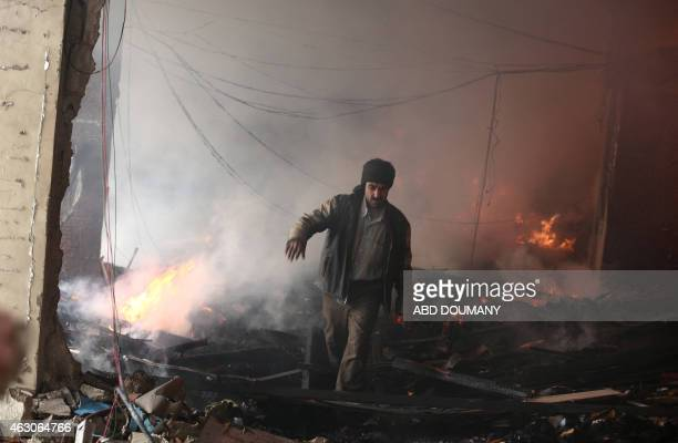 A Syrian man walks amid debris inside a heavily damaged building following reported air strikes by regime forces in the rebelheld area of Douma east...