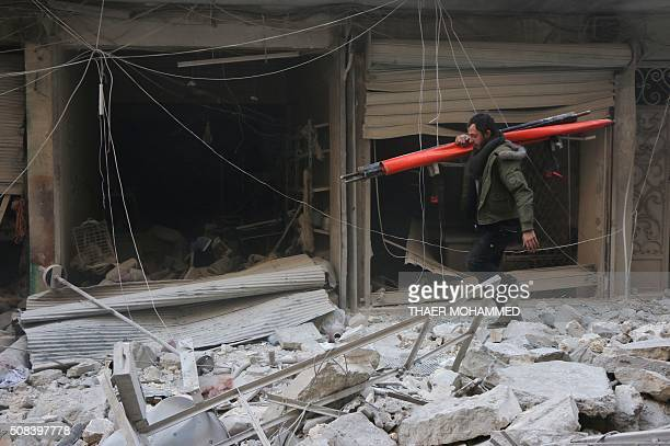 A Syrian man walks amid the rubble of destroyed buildings following a reported air strike on the rebelheld neighbourhood of alKalasa in the northern...