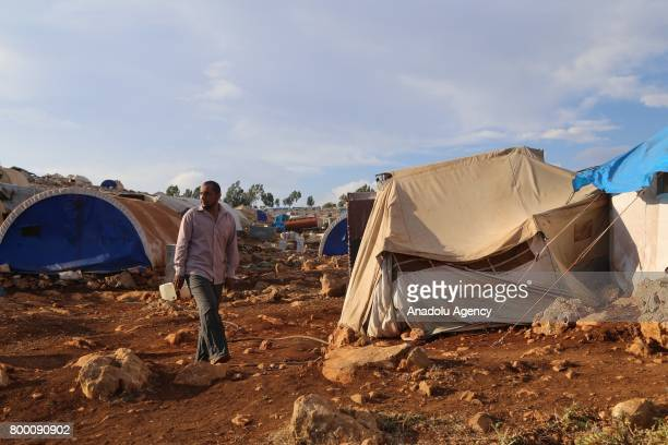 Syrian man walks around in his camp during Muslim's holy month of Ramadan in Idlib Syria on June 23 2017 Ahead of Eid al Fitr Syrian people who fled...