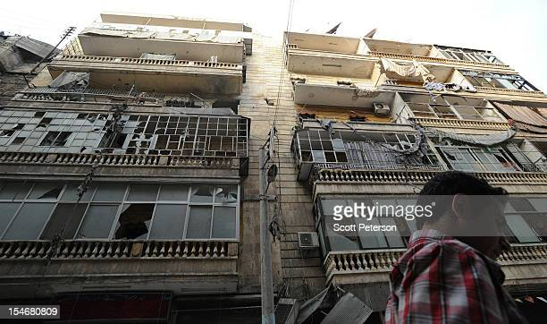 Syrian man walks beneath a damaged building in the Al Shaar district as the intense human and material cost grows from three months of intense...