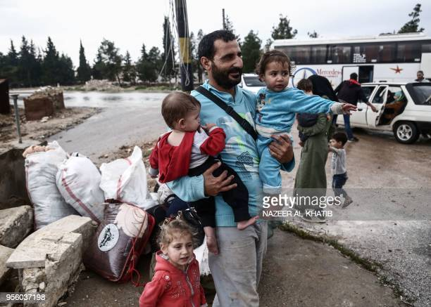 A Syrian man walks carrying children upon arriving in a convoy at Abu alZandin checkpoint near alBab in northern Syria on May 8 after being evacuated...
