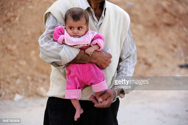 A Syrian man walks down a destroyed street carrying an infant in the former rebelheld Syrian town of Douma on the outskirts of Damascus on April 19...