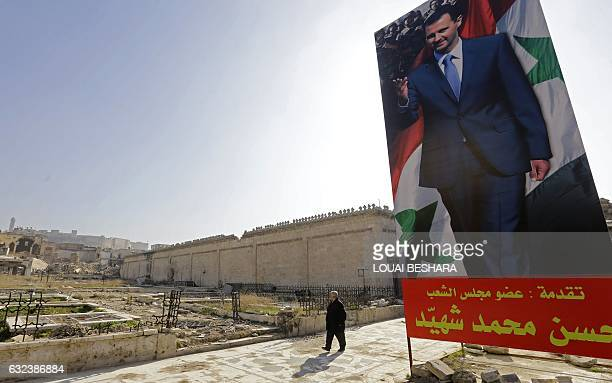 A Syrian man walks next to a large poster of Syrian President Bashar alAssad at the ancient Umayyad Mosque in the old city of Aleppo on January 22 a...