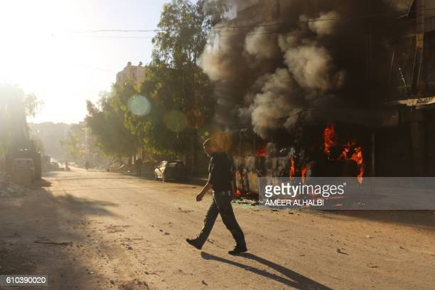 Syrian man walks past a bus set ablaze following a reported air strike in the rebelheld Salaheddin district of Aleppo on September 25 2016 The UN...