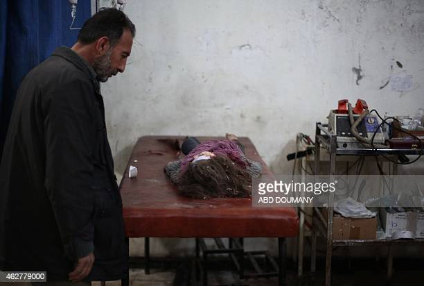 Syrian man walks past a dead child lying on a stretcher at a makeshift clinic following reported air strikes by forces loyal to President Bashar...