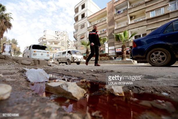 Syrian man walks past a pool of blood following shelling from nearby rebelheld areas on governmentcontrolled areas of the Syrian capital Damascus on...