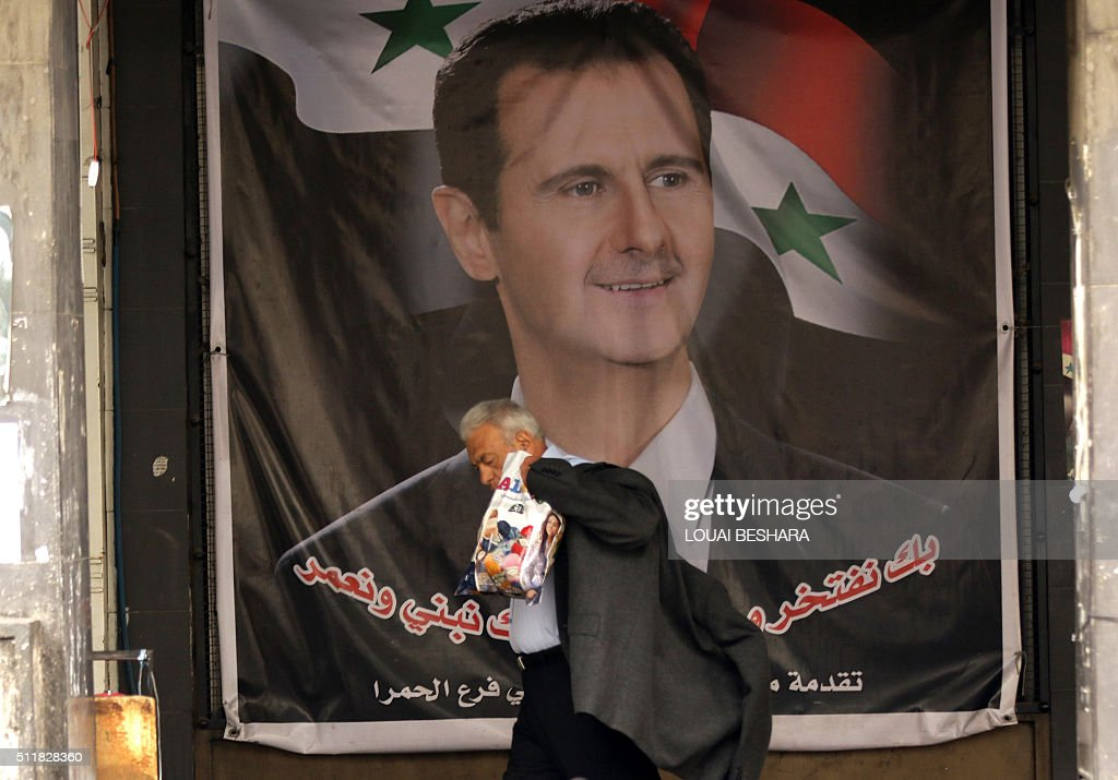 A Syrian man walks past a poster bearing a portrait of Syrian President Bashar al-Assad on a street in the capital Damascus on February 23, 2016, a day after a ceasefire deal was announced. Syria's regime agreed on February 23, 2016 to a ceasefire deal announced the day before by the United States and Russia, but there were widespread doubts it could take effect by the weekend as hoped. The agreement does not apply to jihadists like the Islamic State group and Al-Nusra Front, putting up major hurdles to how it can be implemented on Syria's complex battlefield. BESHARA