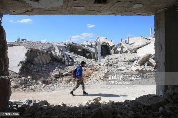 A Syrian man walks past destroyed buildings in a rebelheld area of the southern city of Daraa on November 6 2017 / AFP PHOTO / Mohamad ABAZEED