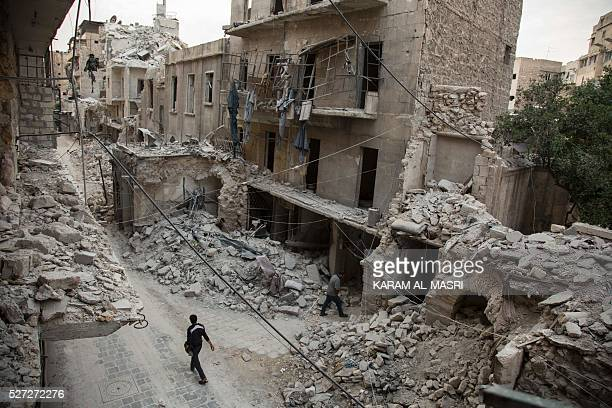 Syrian man walks past destroyed buildings on May 2 in Aleppo's Bab alHadid neighbourhood which was targeted recently by regime air strikes Aleppo...