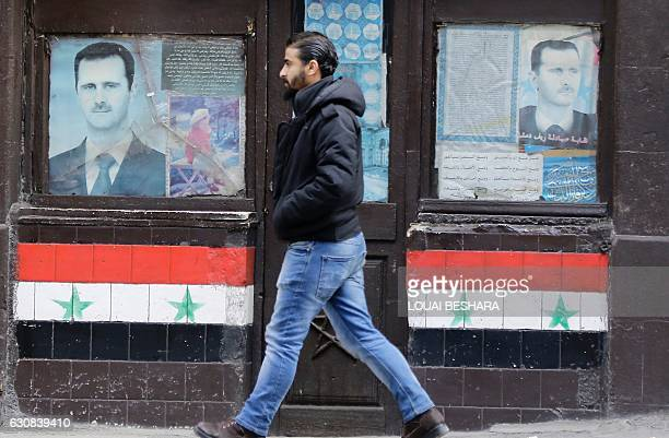 Syrian man walks past posters of Syrian President Bashar alAssad on a shop front in the capital Damascus on January 3 2017 / AFP / LOUAI BESHARA