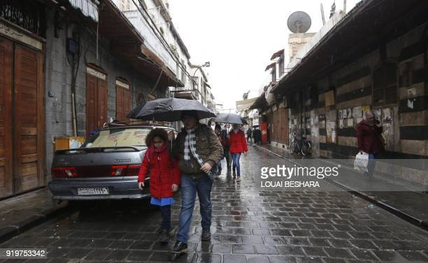 A Syrian man walks with a student as they head to school on February 18 following days of calm in Damascus's Old City that has been bombarded by...