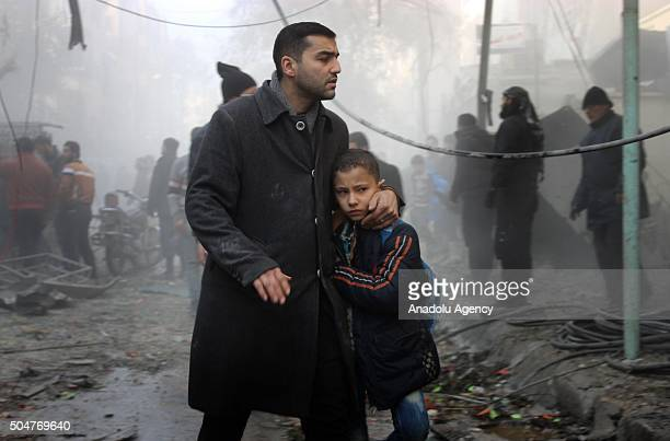 Syrian man walks with his son among ruins after Russian airstrike hits a school at Zibdiyye neighborhood in Aleppo Syria on January 13 2016