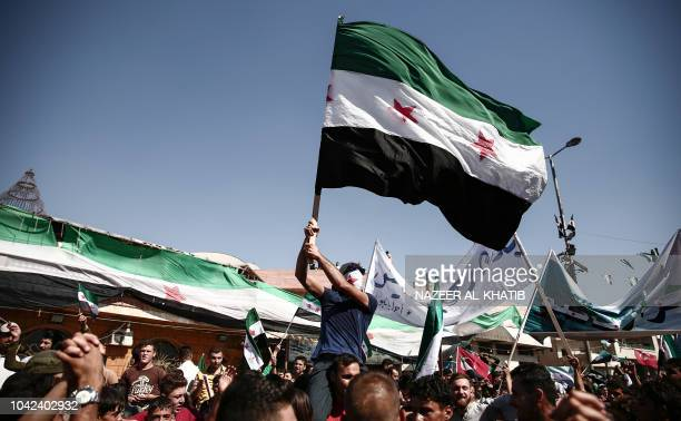 Syrian man waves an opposition flag during a demonstration against the government and calling for the release of those held in its prisons in the...