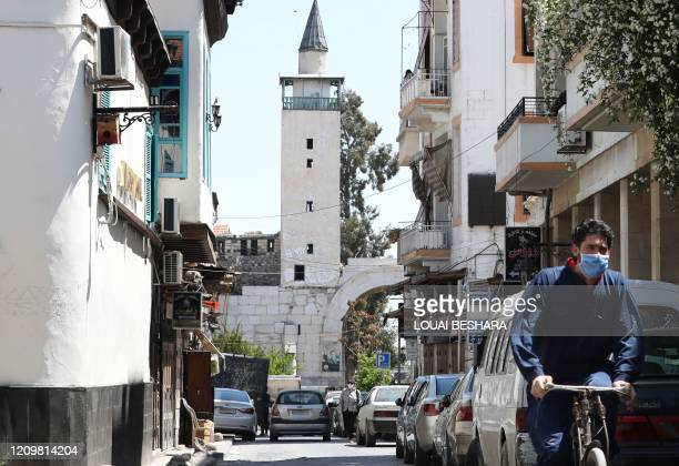 Syrian man, wearing a protective face mask to protect against the coronavirus pandemic, rides his bicycle down a street near the Bab Sharqi gate of...