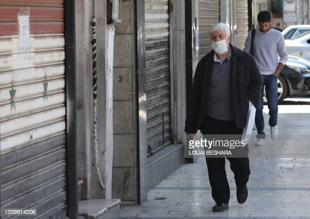 Syrian man, wearing a protective face masks to protect against the coronavirus pandemic, walks down a street in the Salhiyeh neighbourhood of the...