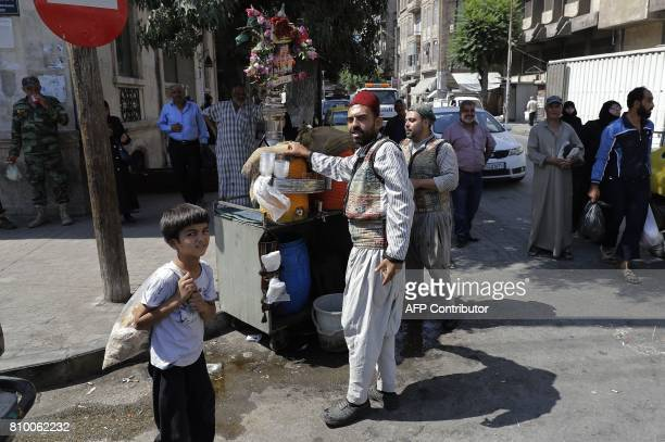 A Syrian man wearing a traditional outfit sells the popular tamarind juice on a street in the northern Syrian city of Aleppo on July 6 2017 / AFP...