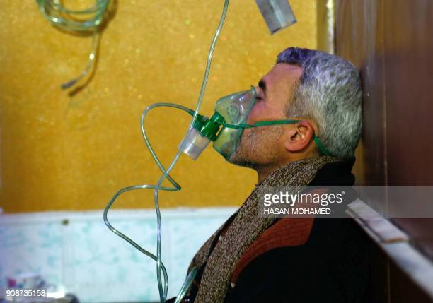 A Syrian man wears an oxygen mask at a makeshift hospital following a reported gas attack on the rebelheld besieged town of Douma in the eastern...