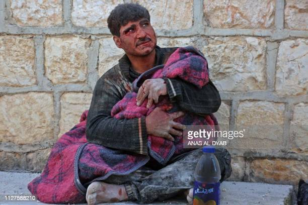 Syrian man weeps as he cradles the body of his daughter who was killed following reported shelling in the town of Khan Sheikhun in the southern...