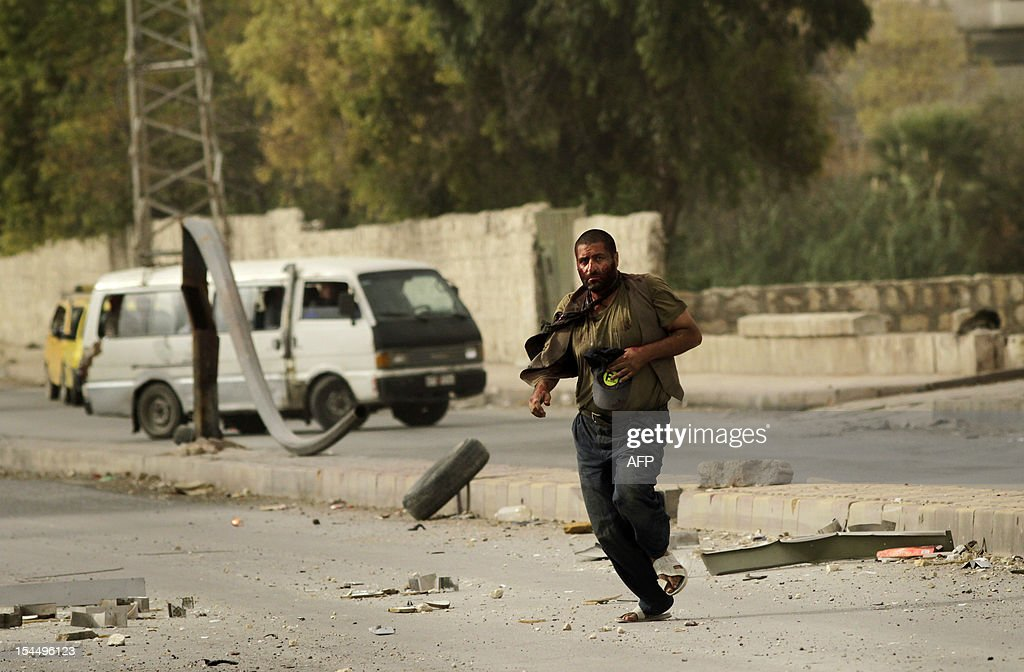 A Syrian man who was shot by a sniper runs towards members of the Al-Baraa Bin Malek Batallion, part of the Free Syria Army's Al-Fatah brigade, in the Bustan al-Basha district of the northern city of Aleppo on October 20, 2012. Due to the risk of being shot by the sniper, no one was able to rescue the wounded man who eventually ran towards rebels, only to be shot by the sniper a second time. Rebels then pulled him and rushed him to a hospital, though it is not known if he survived. Three civilians were shot on this main road in the space of three hours by the same sniper.