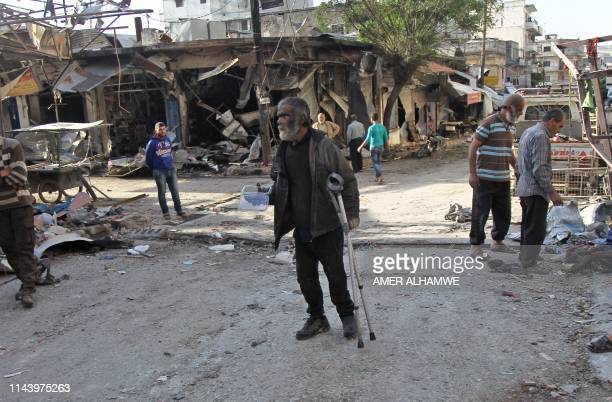 Syrian man whose shop was destroyed in a regime aerial bombardment the previous day walks around the area on May 15 2019 in Jisr alShughur in Syria's...
