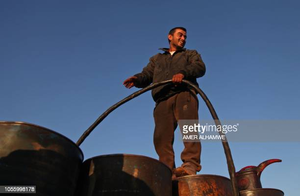 A Syrian man works on November 1 2018 at a primitive oil facility in the town of Zardana in the countryside of the northwestern Syrian Idlib province...