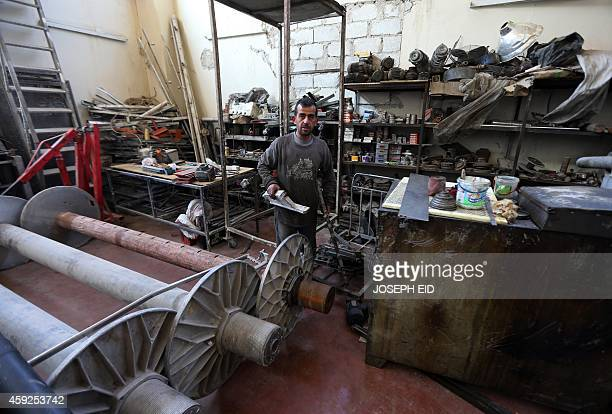 Syrian mechanic works at his workshop in Aleppo's industrial area in the government controlled side of the wartorn northern Syrian city on November...