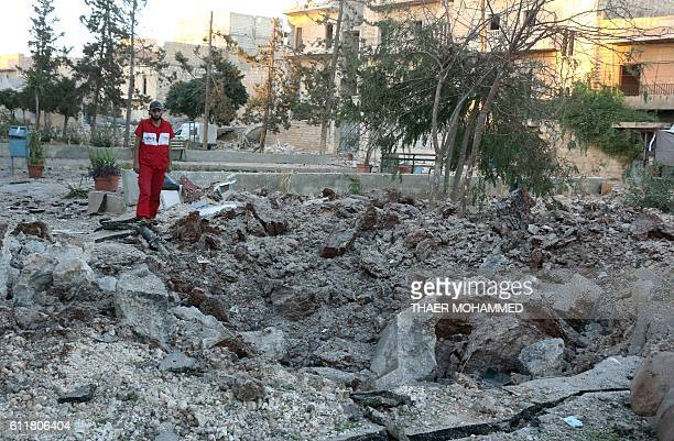A Syrian medical staff member inspects the damage at the site of a medical facility after it was reportedly hit by Syrian regime barrel bombs on...