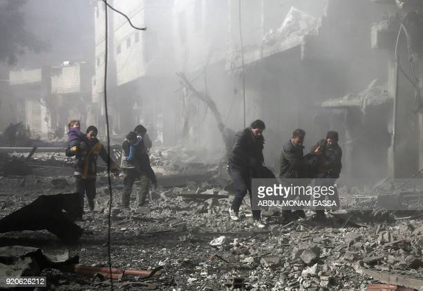Syrian men carry an injured victim amid the rubble of buildings following government bombing in the rebelheld town of Hamouria in the besieged...