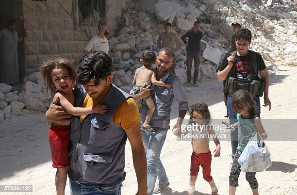Syrian men carry injured children amid the rubble of destroyed buildings following reported air strikes on the rebelheld neighbourhood of AlMashhad...