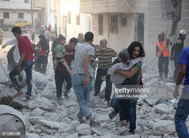 TOPSHOT Syrian men carry injured people amid the rubble of destroyed buildings following a reported air strike on the rebelheld northwestern city of...