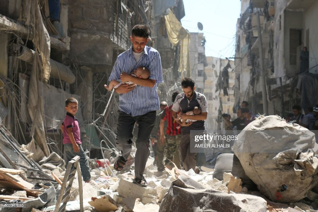 TOPSHOT - Syrian men carrying babies make their way through the rubble of destroyed buildings following a reported air strike on the rebel-held Salihin neighbourhood of the northern city of Aleppo, on September 11, 2016. Air strikes have killed dozens in rebel-held parts of Syria as the opposition considers whether to join a US-Russia truce deal due to take effect on September 12. /
