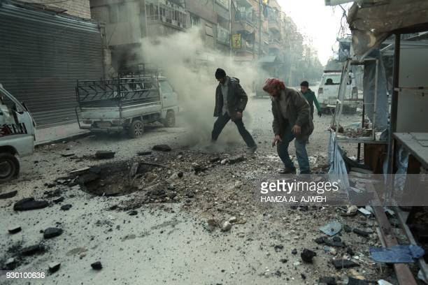 TOPSHOT Syrian men check the damage following Syrian government shelling on the town of Douma in the rebelheld enclave of Eastern Ghouta on the...