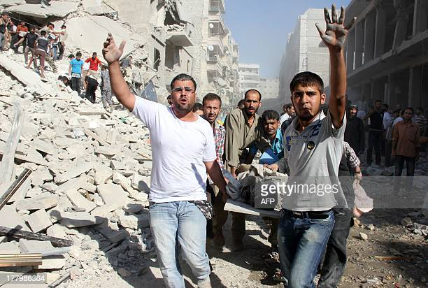 Syrian men evacuate a victim following an air strike by regime forces in the northern city of Aleppo on August 26 2013 Syria's opposition accused...